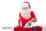Happy santa claus ironing his jacket