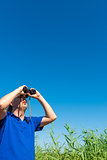 man looking through binoculars into the sky