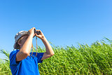 man looks for through the reeds with binoculars
