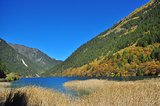 Lake with straw on a valley with trees