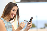 Happy woman buying online with a smart phone