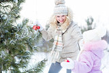 Happy mother and child playing with christmas tree decorations outdoor