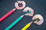 Different color pencils shavings on dark background