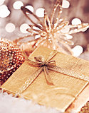 Golden Christmas gift with baubles decorations