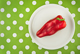 Red pepper on white plate, top view