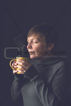 Beautiful Woman Smelling Hot Coffee in Dark Room