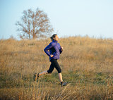 Young Sports Woman Running on the Trail in the Autumn Field