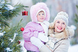 Happy mother and child with decorated christmas tree outdoor wintertime