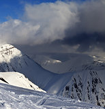 Off-piste slope and mountains with storm clouds