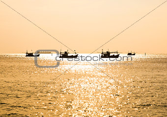 Fishing boat silhouette at sunset in sea