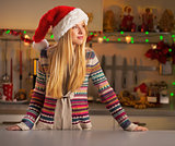 Portrait of young woman in christmas decorated kitchen looking o