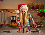 Portrait of smiling teenager girl in santa hat in christmas deco