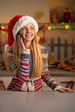 Happy teenager girl in santa hat talking cell phone in christmas