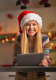 Portrait of happy teenager girl in santa hat using tablet pc