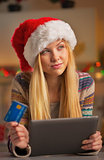 Portrait of thoughtful teenager girl in santa hat with credit ca