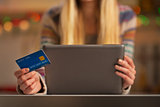 Closeup on teenager girl with credit card using tablet pc
