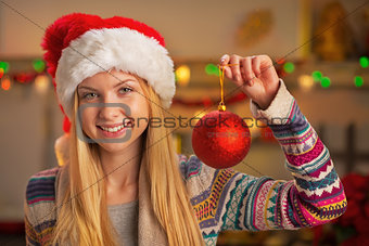 Portrait of smiling teenager girl in santa hat showing christmas