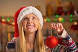 Happy teenager girl in santa hat holding christmas ball and look