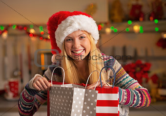 Portrait of happy teenager girl in santa hat with shopping bags