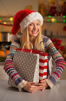 Portrait of happy teenager girl in santa hat hugging shopping ba