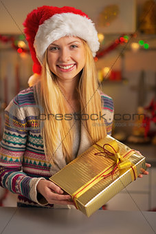 Portrait of smiling teenager girl in santa hat with christmas pr