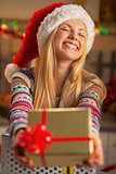 Happy teenager girl in santa hat giving christmas present box