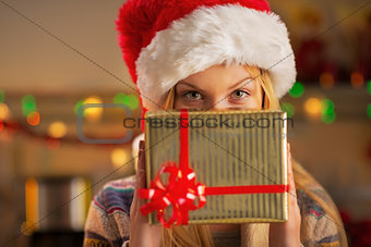 Portrait of teenager girl in santa hat hiding behind christmas p