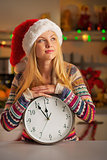 Portrait of teenager girl in santa hat with clock