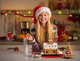 Portrait of smiling teenager girl in santa hat decorating christ