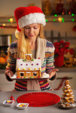 Happy teenager girl in santa hat holding christmas cookie house