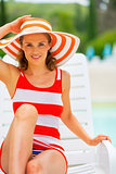Portrait of happy young woman in hat sitting on sunbed