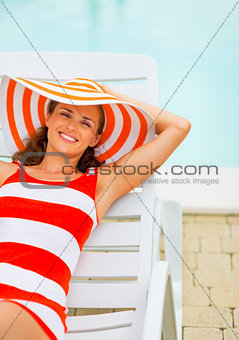 Portrait of smiling young woman in hat sitting laying on chaise-