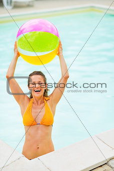 Portrait of smiling young woman with beach ball in pool
