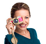 Happy woman holding pink camera on white background