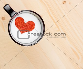 top of view of cup of milk with decorative heart on wood table, concept of valentine day