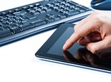 hand touching tablet near keyboard, concept of new technology