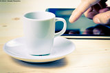 cup of coffee in front of the tablet, concept of new technology