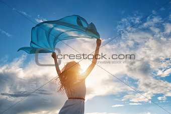 Beautiful young woman holding blue scarf on the wind