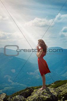 Beautiful woman praying in mountain landscape