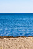 Small beach on blue water on white sky