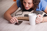 girl enjoying her mobile while drinking from a mug