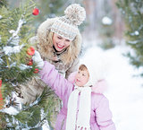 Happy family mother and child playing with christmas tree decoration outdoor