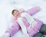 Happy kid lying on snow in winter outdoor