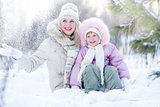 Happy family mother and daughter sitting in snow outdoor wintertime