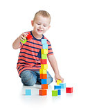 Kid playing and building high tower with colorful blocks isolated