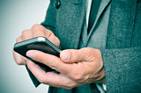 businessman in coat using a smartphone
