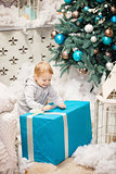 Toddler boy opening a box with Christmas gift
