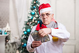 Senior man in Santa's hat holding money over Christmas background