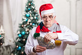 Senior man in Santa's hat holding money on Christmas background