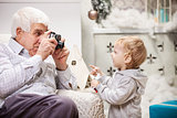 Senior man taking photo of his toddler grandson while sitting near Christmas tree at home